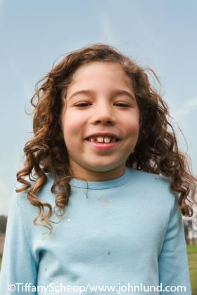 Picture of a happy smiling little girl around 6 or 7 years old with shoulder length curly hair and a light blue shirt